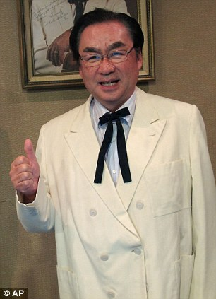 Original recipe: The head of KFC in Japan tries on Col Sanders' trademark suit which he bought for $21,510