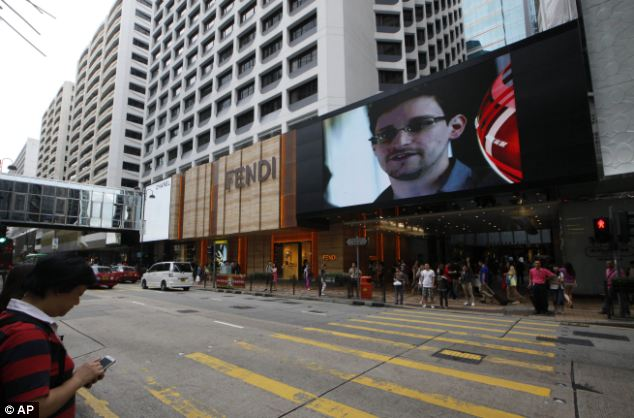 Making headlines: A news report featuring Edward Snowden is broadcast from a giant screen near where he was hiding in Hong Kong