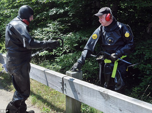 Searching: State police wearing wetsuits and armed with metal detectors searched a stream near Aaron Hernandez's North Attleboro, Massachusetts, home on Monday