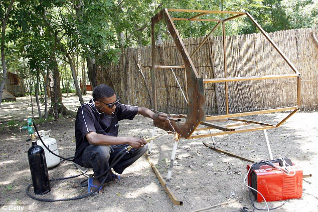 Starting out: Aminu Abubakar can be seen welding the skeleton of a his helicopter out of scrap metal in 2007