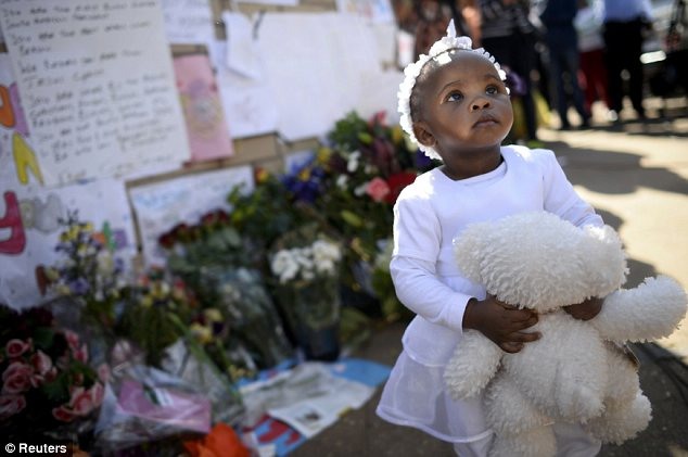 Support: A girl holding a teddy bear stands in front of the wall of tributes left to the anti-apartheid icon