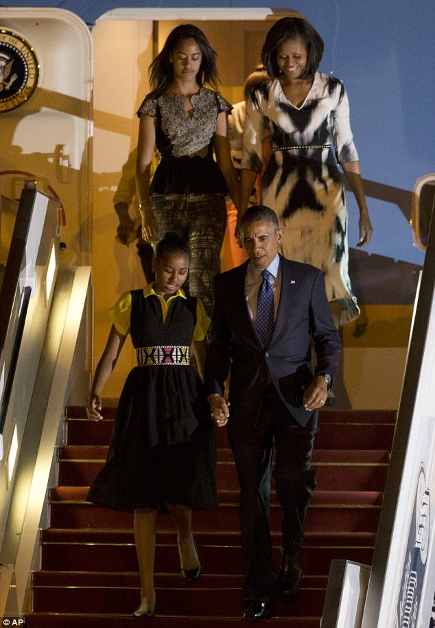 Arrived safely: President Barack Obama holds his daughter Sasha's hand as the he and his family exit Air Force One after landing in Dakar, Senegal