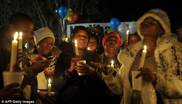 Vigil: Well-wishers hold candles as they pray outside the former president's hospital on Wednesday night