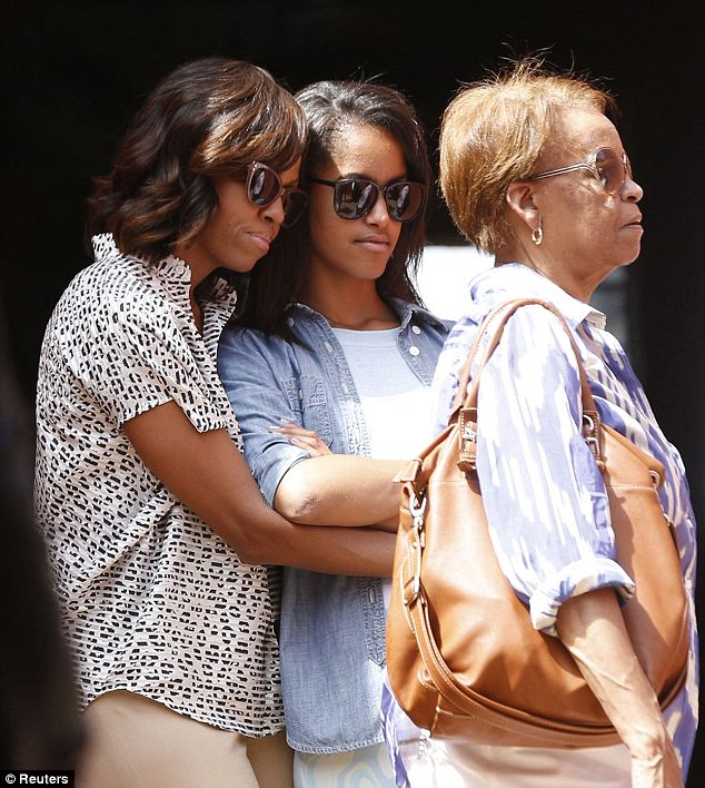 Close hold: Mrs Obama gives Malia a hug during a tour of the island alongside her mother Mrs Robinson, who lives with the family in the White House