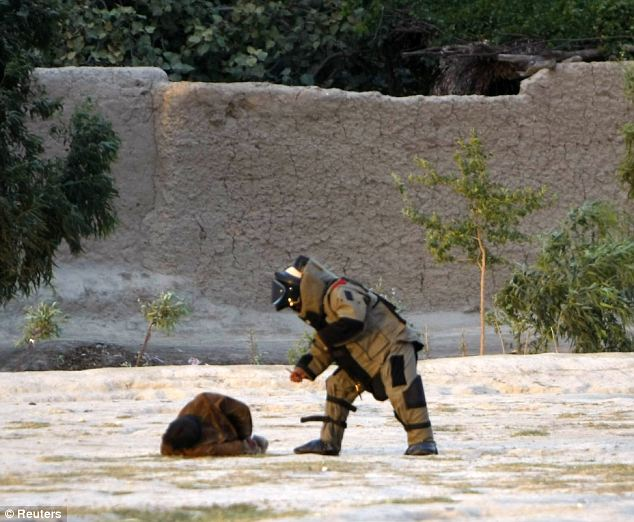 Dangerous work: A member of the Afghan bomb disposal unit approaches a suicide attacker to defuse his explosive vest after he was captured before detonating it in Jalalabad province earlier today