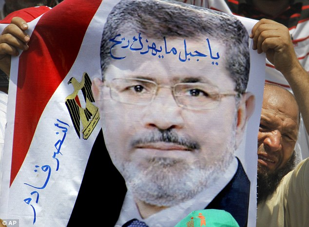 A supporter of Egypt's Islamist President Mohammed Morsi holds his poster during a rally outside the Rabia el-Adawiya mosque near the presidential palace in Cairo
