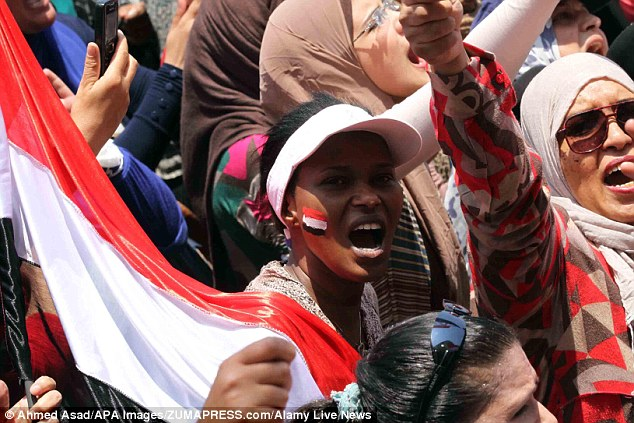 One woman has painted a flag on her cheek and shouts during the historical protest today in Cairo