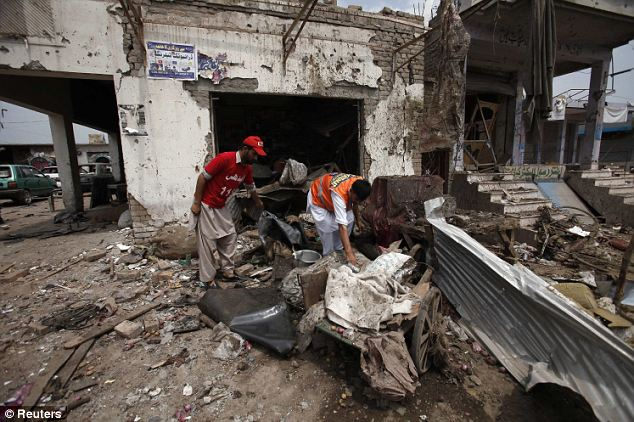 Violence: Rescue workers collect evidence at the site of the Peshawar bomb attack, which killed 17 people