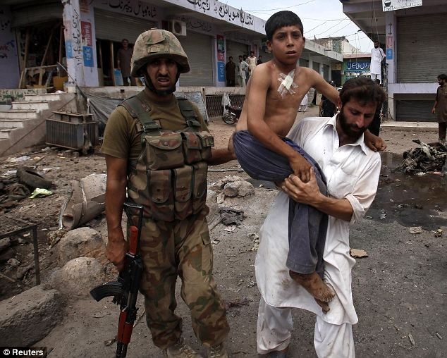 Ongoing: A man carries a boy who was injured in a bomb attack from the site in the outskirts of Peshawar today