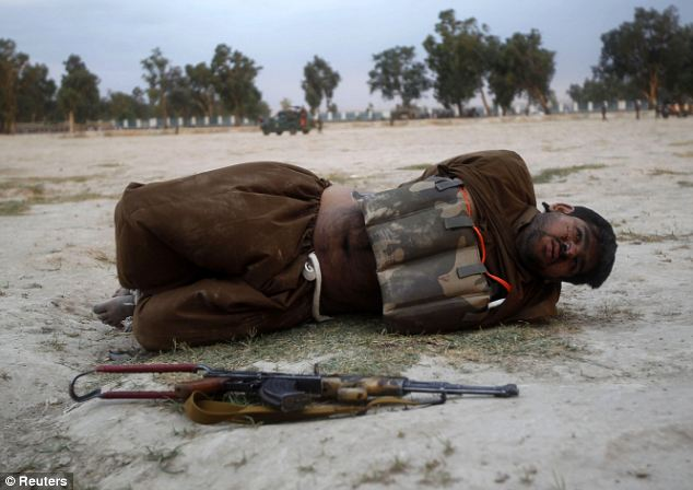 The would-be martyr lies on the ground after his vest was defused: Before the suspected terrorist could be taken in for interrogation, the experts had to be called in for the risky job of disarming the bomb
