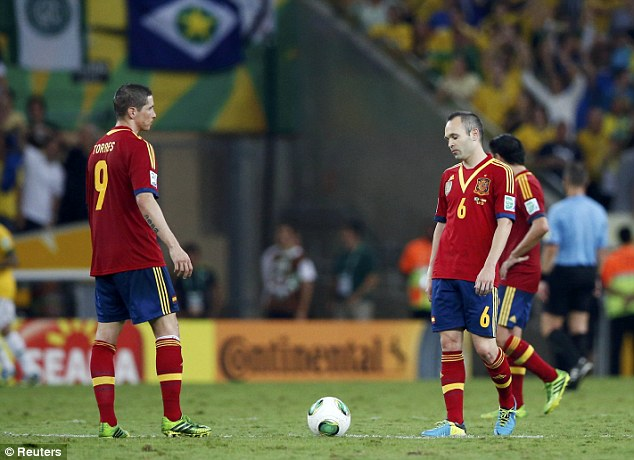 Humbled: Andres Iniesta and Torres look reluctant to re-start the game after the third goal of the night
