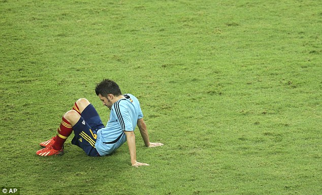 Contrast: David Villa sits on the pitch after Spain were humbled at the Maracana