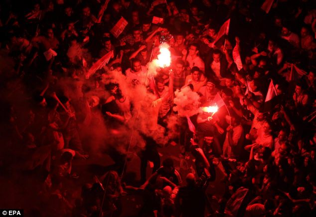 Protestors dance with flares as they demonstrate against President Morsi, in Tahrir square, Cairo
