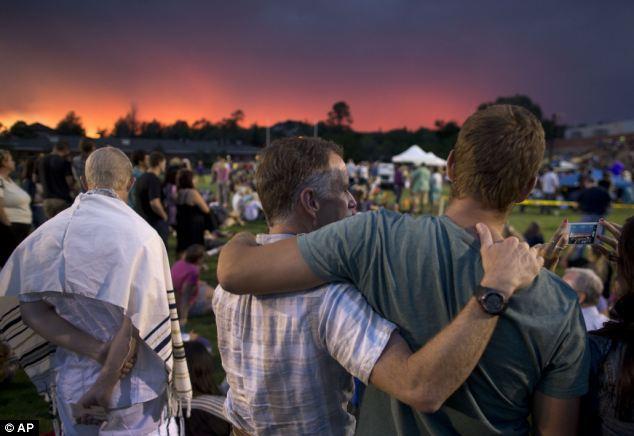 Sad scene: The sun sets as mourners gather