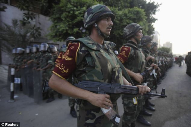 Army soldiers stand guard in front of protesters near the Republican Guard headquarters in Cairo