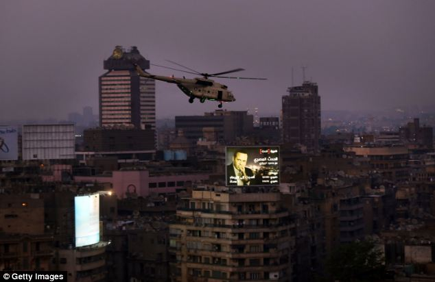 An Egyptian military helicopter flies over Tahrir Square after a broadcast by the head of the military confirming they will temporarily be taking over