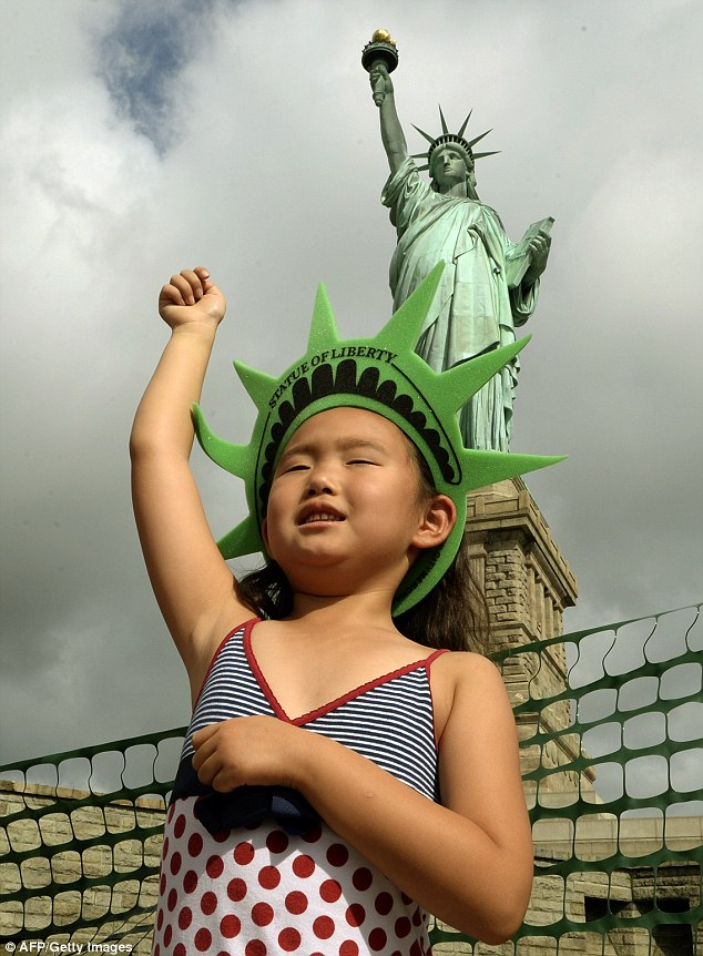 Symbol for the world: Sofia Dagbaborj, from Mongolia, poses in front of Lady Liberty on Independence Day after Liberty Island is reopened eight months after Superstorm Sandy damaged it