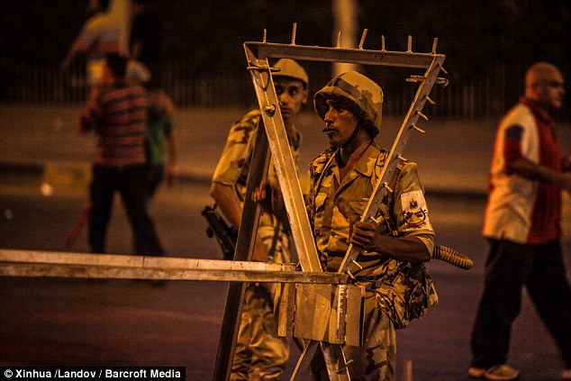 Containment strategy: Egyptian soldiers build a roadblock in Nasr City where supporters of President Morsi supporters were protesting