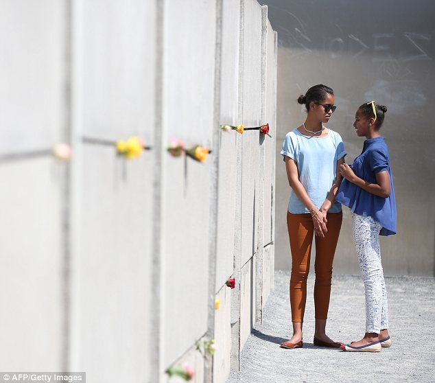 Poignant: Malia (left) and Sasha visit the Berlin Wall memorial on June 19