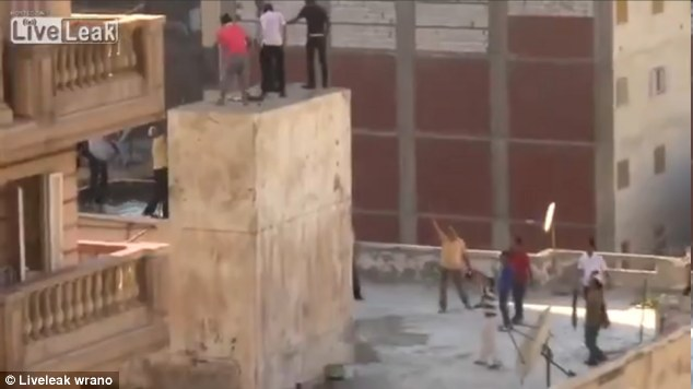 Trapped: The mob gather around the young men as the fourth teen manages to climb onto to ledge, and they begin throwing rocks at them to get them down