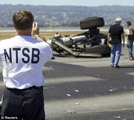 Investigation: U.S. National Transportation Safety Board (NTSB) investigators attend to the scene of the Asiana Airlines Flight 214 crash site at San Francisco International Airport in San Francisco, California on Sunday