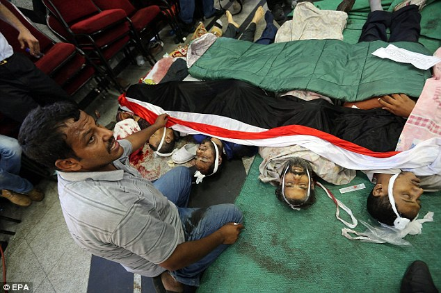 Victims: A member of the Muslim Brotherhood sits next to the bodies of supporters of ousted president Morsi who were killed during clashes early on Monday morning