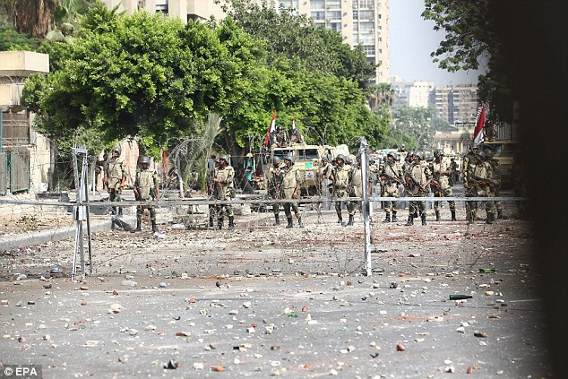 Out in force: Egyptian Republican guards take up positions in front of a barricade during clashes with members of the Muslim Brotherhood near rabaa aldwya in Cairo
