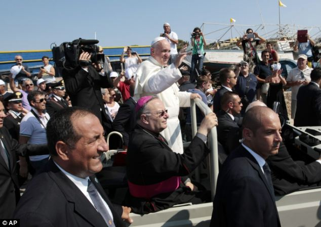 Pope Francis delivers his blessing as he is driven through the crowd during his visit to the island of Lampedusa