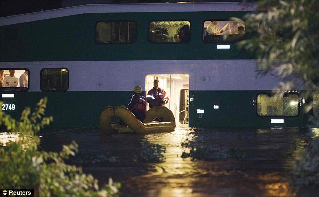 Rescue: Emergency workers brought a dingy to the door of the commuter train to evacuate its passengers