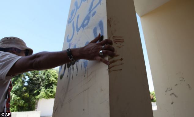 A Libyan man told the Associated Press that bloodstains outside the Benghazi consulate were from an American staff member who grabbed the edge of the column while he was evacuated