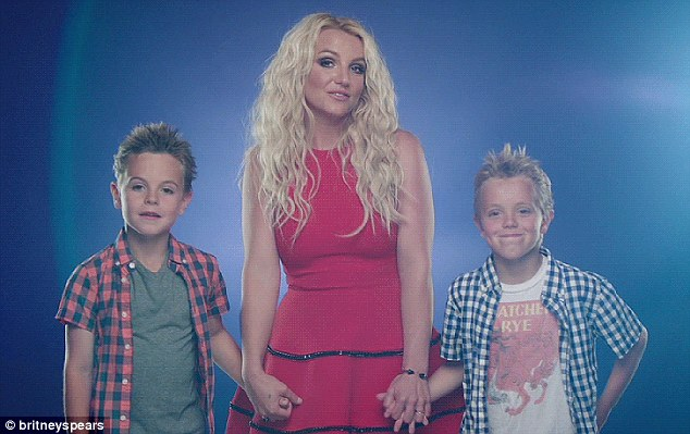 Hand-in-hand: Dressed in a red dress, Britney is also seen holding both of her boys' hands in the clip