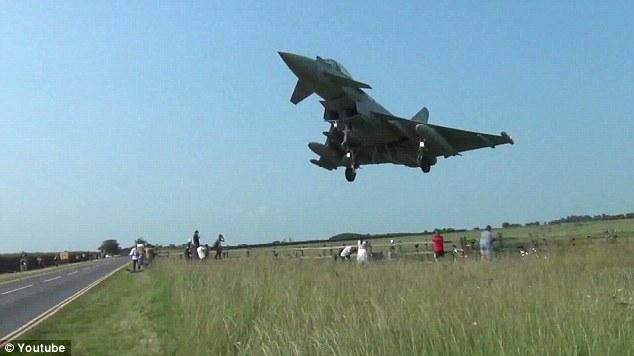 Get down! Plane spotters watching an air show cower as a Typhoon jet flies just a few feet above them