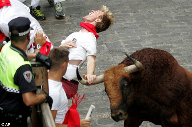 Vicious: Mr Eccles winces in pain as he is gored by a bull - six people in total were taken to hospital after today's run