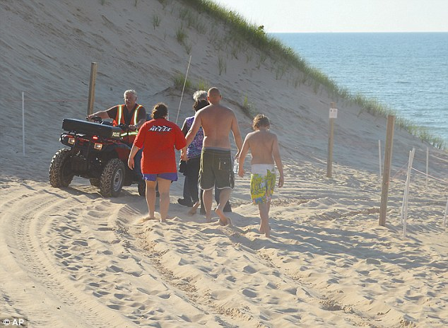Vacationers: Family members of the 6-year-old boy who was buried in the sand at Mount Baldy are escorted to the beach by a Michigan City Police Department chaplain