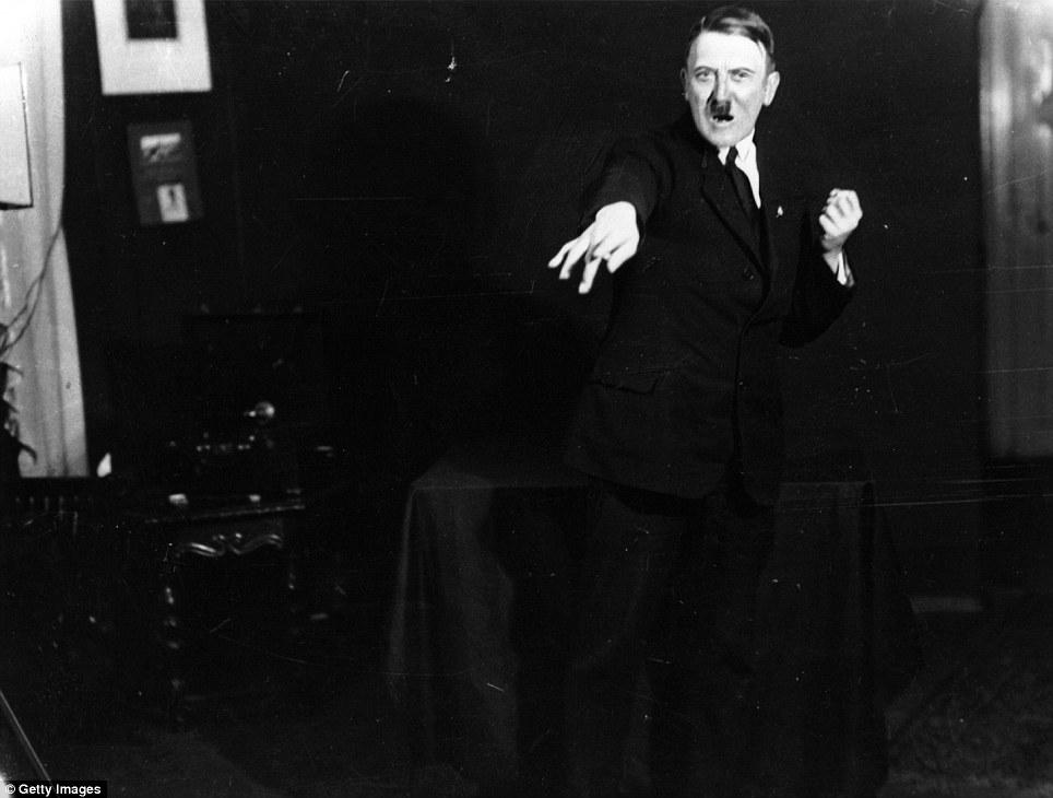 Hitler gesticulates towards an imaginary crowd while listening to a playback recording of his own speech