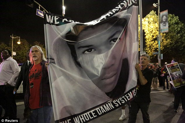Challenging the system: Protesters hold an image of Trayvon Martin while marching in the Leimert Park area of Los Angeles, California