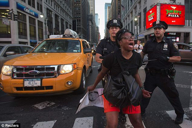Flare up: Police try to calm a screaming protestor in Manhattan. Tensions flared as a group of thousands marched toward Harlem late Sunday and arrests began before 11pm