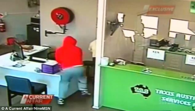 Fear: Mr Khan (in white shirt) was dragged into the office with a knife in his back to get the cas