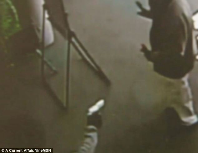 Sickening: Their father holds his hands up as the gunman takes aim before forcing him to hand over cash