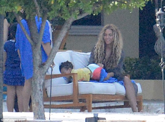 Off they come: Beyoncé takes her daughter's leggings off so she can play around the pool
