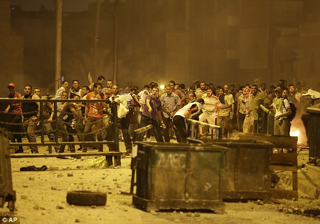 Further violence: Supporters of ousted President Mohammed Morsi throw stones against his opponents and security forces as a protest turned violent in downtown Cairo