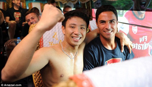 Keeping the pace: Arsenal's Mikel Arteta poses with 'The Running Man' on the Gunners team coach