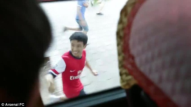 Touching distance: The Running Man attempts to keep pace with the Arsenal team bus