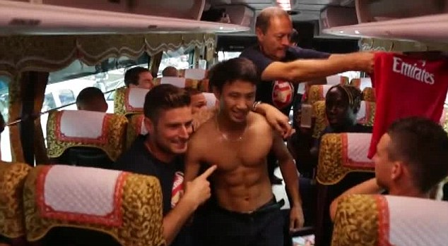 In good shape: Arsenal players were impressed with the fan's six-pack as his shirt was passed round to be signed