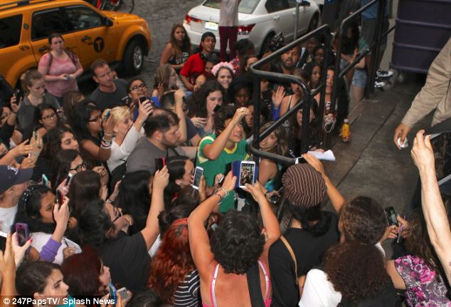 Mobbed by fans: Harry Styles had to climb out of a crowd to escape his desperate fans