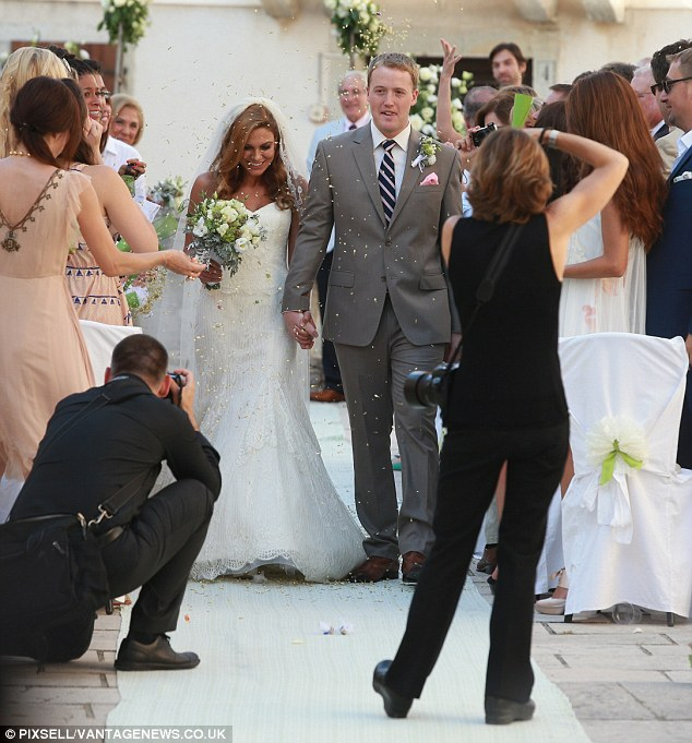 The happy couple: Yasemin Denari and McLain Southworth are snapped by photographers as guests toss confetti at the ceremony