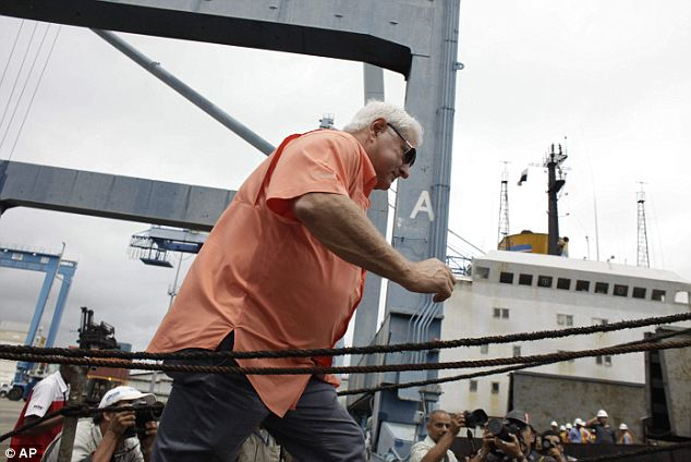 Panama's President Ricardo Martinelli walks up a ramp to the North Korean-flagged ship. He would later post photos of the missiles to Twitter