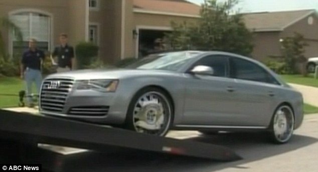 Pay back: Wilson's $90,000 Audi A8 is towed from her Florida home