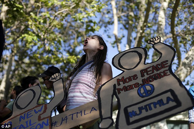 West Coast in uproar: Kalisa Myers, 31, chants her slogans standing behind cutouts representing Trayvon Martin during a demonstration