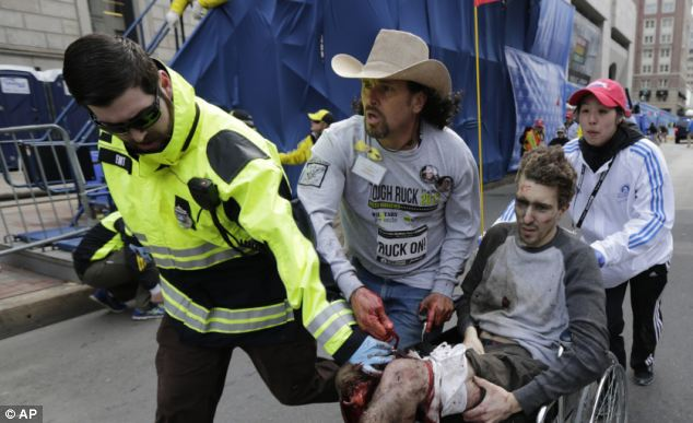 An emergency responder and two volunteers, including Carlos Arredondo, center, push Jeff Bauman in a wheel chair after he was injured in the explosion near the finish line of the Boston Marathon on April 15